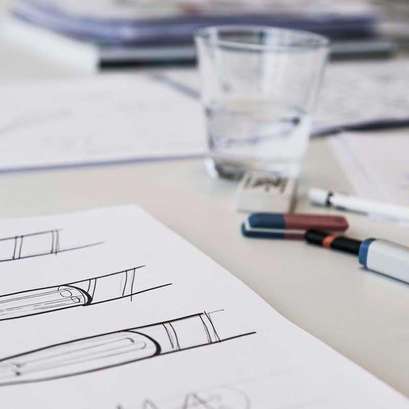 Stukje papier met een schets, wat viltstiften en een glas water. Foto door Claudette van de Rakt 2019 Lighthouse