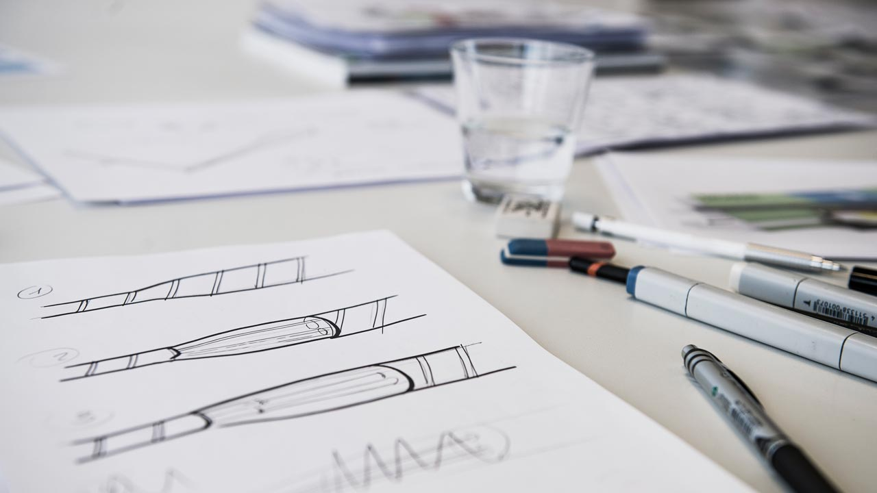 Een foto met een paar schetsen, potloden en viltstiften. Op de achtergrond staat een glas water.