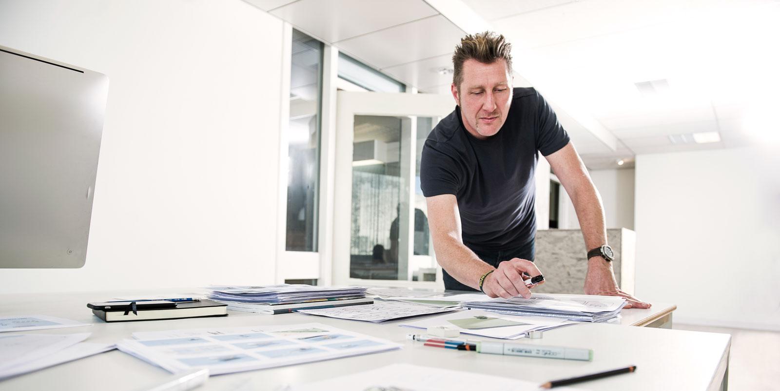 Man aan het tekenen in een creatieve studio, witte omgeving, bureau met tekningen en markers